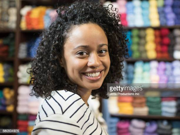Mixed race woman smiling in yarn store