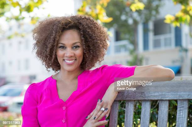 mixed race woman smiling on bench - one mid adult woman only stock pictures, royalty-free photos & images
