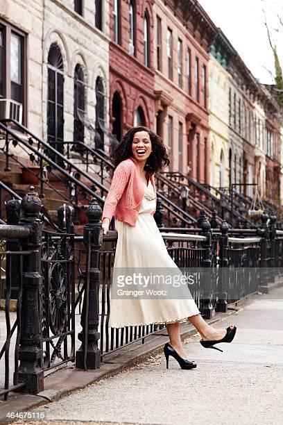 mixed race woman smiling on city street - もたれる ストックフォトと画像