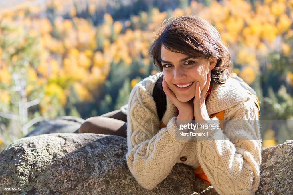 Mixed race woman smiling on rock : Foto stock