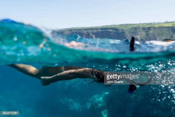 Mixed race woman snorkeling in tropical ocean