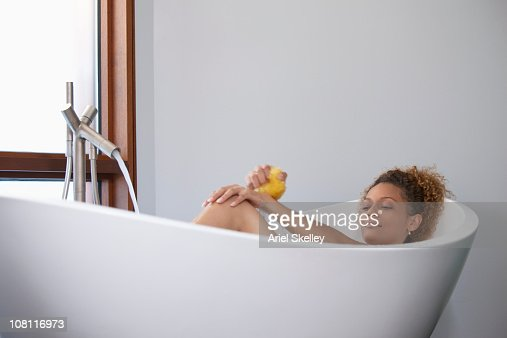 Mixed Race Woman Soaking In Bathtub Stock Photo | Getty Images