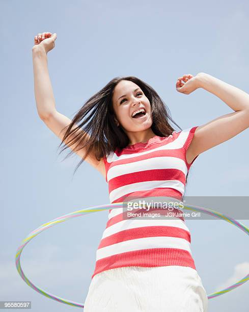 Mixed race woman spinning hula hoop