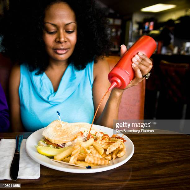 Mixed race woman squeezing ketchup on french fries in diner booth