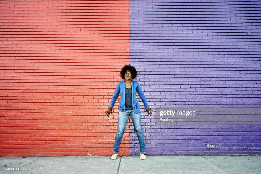 Mixed race woman standing by colorful wall : Stock Photo