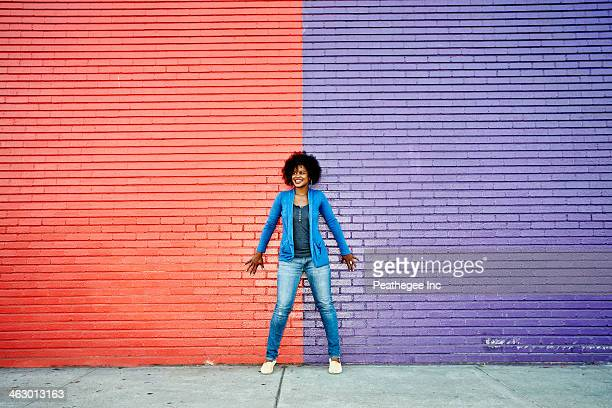 mixed race woman standing by colorful wall - bontgekleurd stockfoto's en -beelden