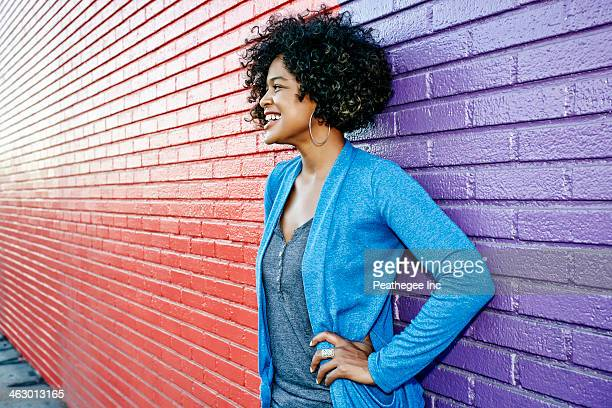 mixed race woman standing by colorful wall - one mid adult woman only stock pictures, royalty-free photos & images