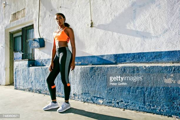 mixed race woman standing near urban wall - sportswear stock pictures, royalty-free photos & images