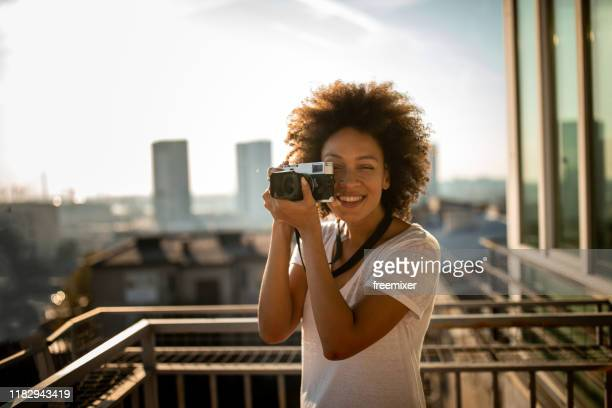 mixed race woman standing on balcony and taking a photography - digital camera stock pictures, royalty-free photos & images