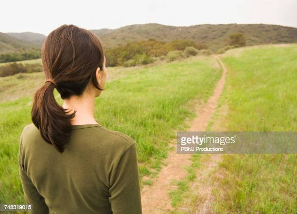 Mixed Race woman standing on path in field
