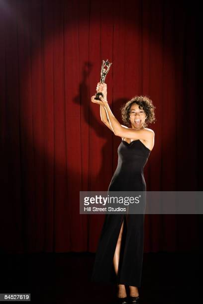 mixed race woman standing on stage with trophy - actress stock pictures, royalty-free photos & images
