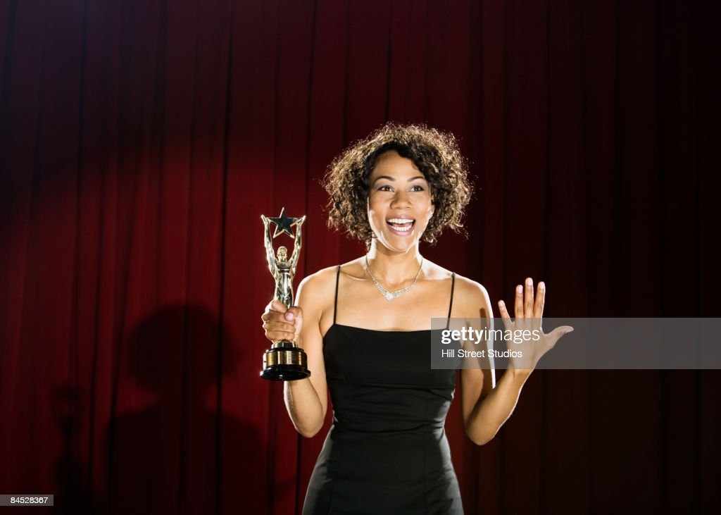 Mixed race woman standing on stage with trophy : Stock Photo