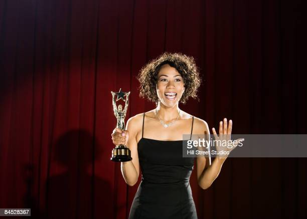 mixed race woman standing on stage with trophy - award stock pictures, royalty-free photos & images