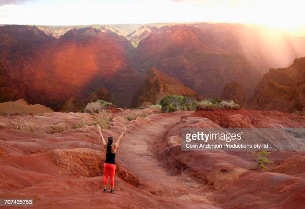 Mixed Race woman standing with arms raised in sunny landscape