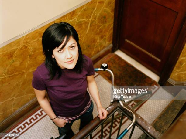 Mixed race woman standing with bicycle in apartment hallway
