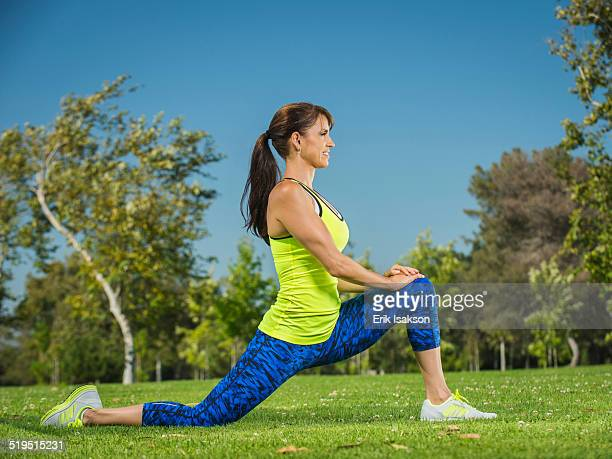 Mixed race woman stretching in park