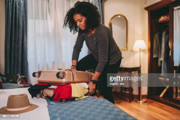 mixed race woman struggling with overflowing suitcase before journey - chiuso per ferie foto e immagini stock