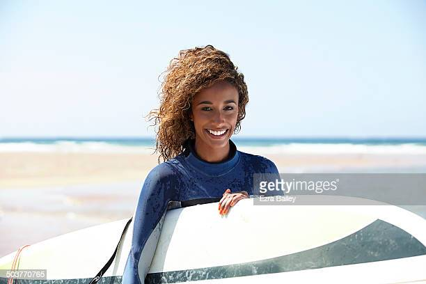 Mixed race woman surfer on the beach