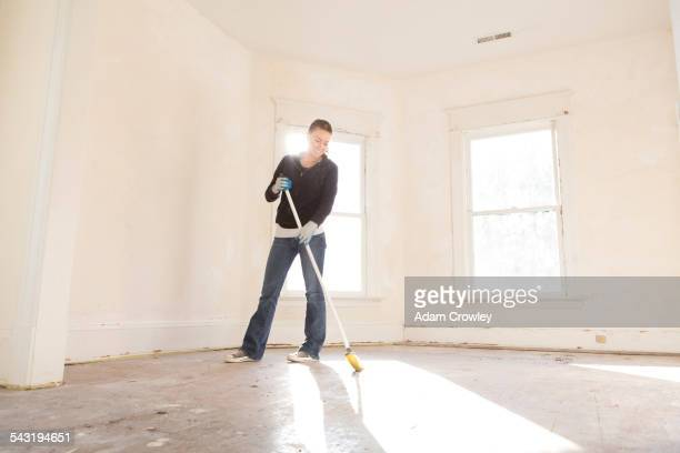 Mixed race woman sweeping floor of new home