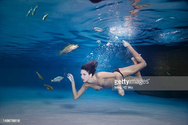 Mixed race woman swimming in water with fish
