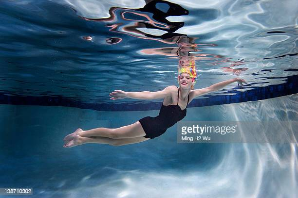 Mixed race woman swimming underwater