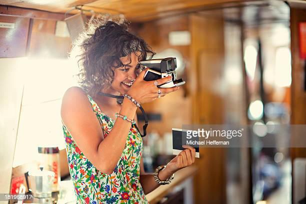 mixed race woman takes polaroid photograph
