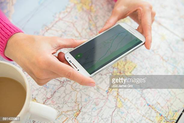 Mixed race woman taking cell phone photograph of roadmap