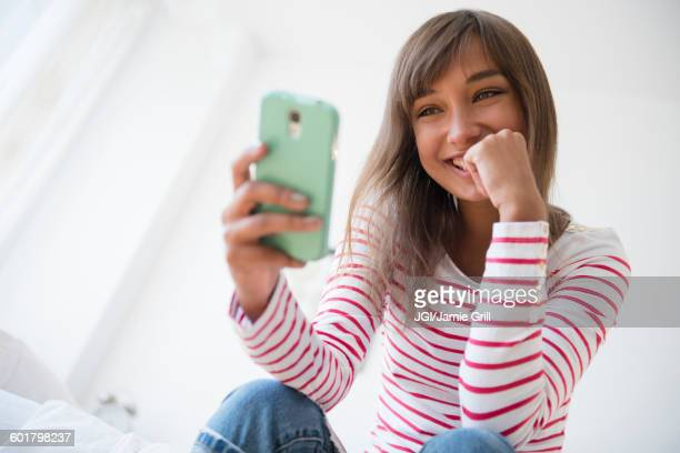 Mixed race woman taking selfie with cell phone