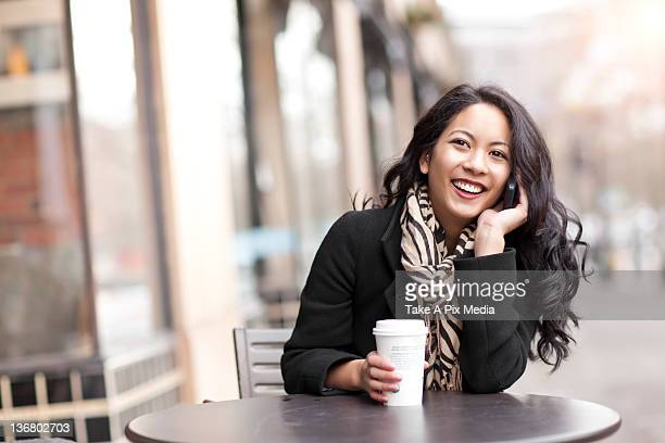 mixed race woman talking on cell phone and drinking coffee - one young woman only stock pictures, royalty-free photos & images