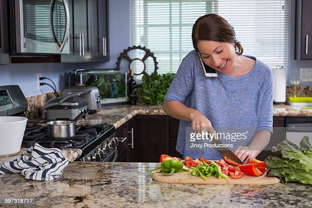 Mixed race woman talking on phone and chopping vegetables
