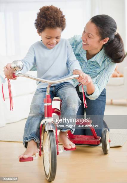 Mixed race woman teaching son to ride tricycle