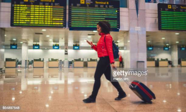 Mixed race woman texting at the airport terminal