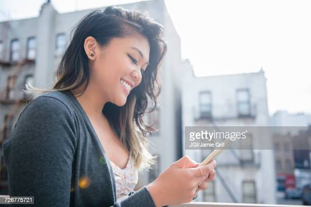 Mixed Race woman texting on cell phone in city