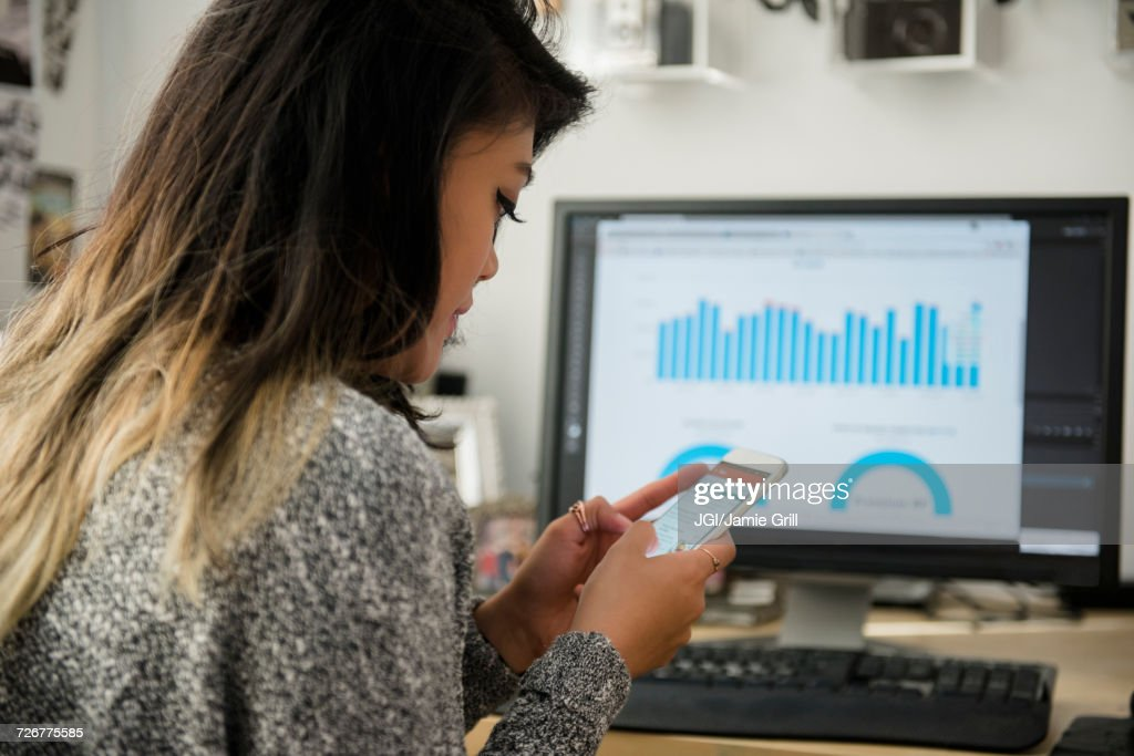 Mixed Race woman texting on cell phone near computer : Stock Photo