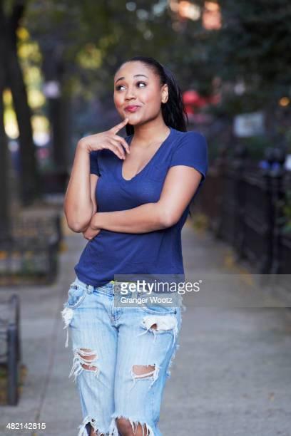 Mixed race woman thinking on urban sidewalk