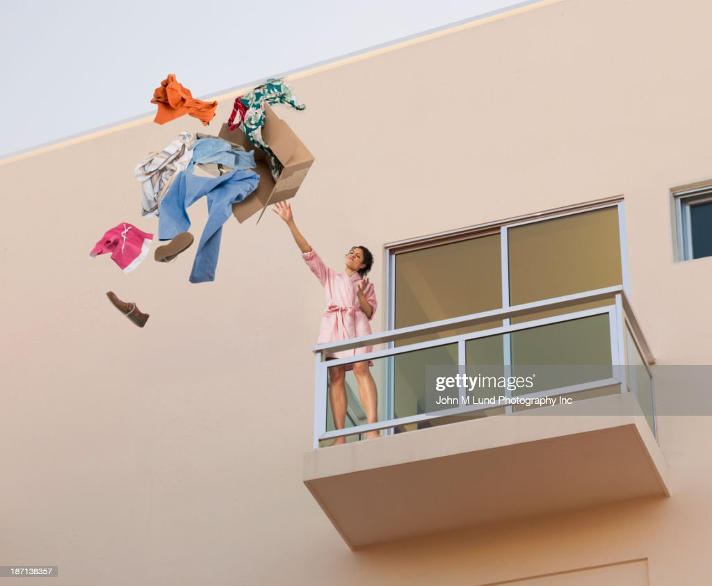 Mixed race woman throwing clothes off balcony : Stock Photo