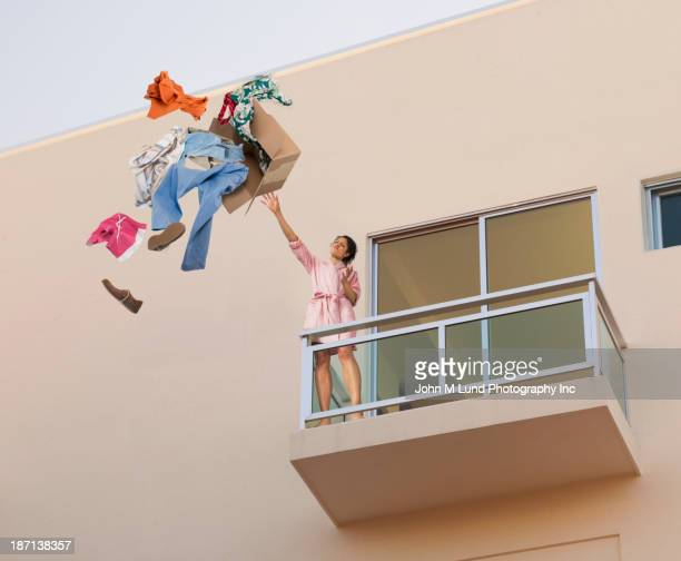 mixed race woman throwing clothes off balcony - lanciare foto e immagini stock