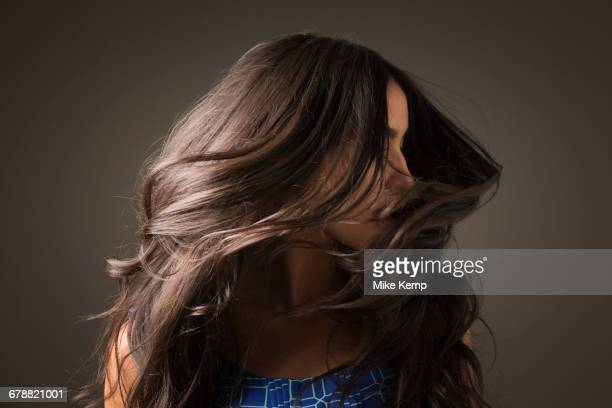 mixed race woman tossing hair - lang haar stockfoto's en -beelden