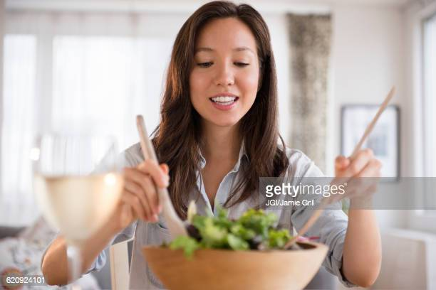 Mixed race woman tossing salad