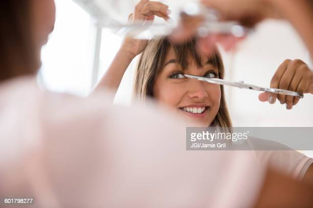 Mixed race woman trimming her bangs