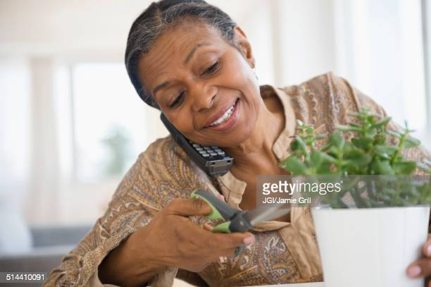 Mixed race woman trimming plant and talking on phone