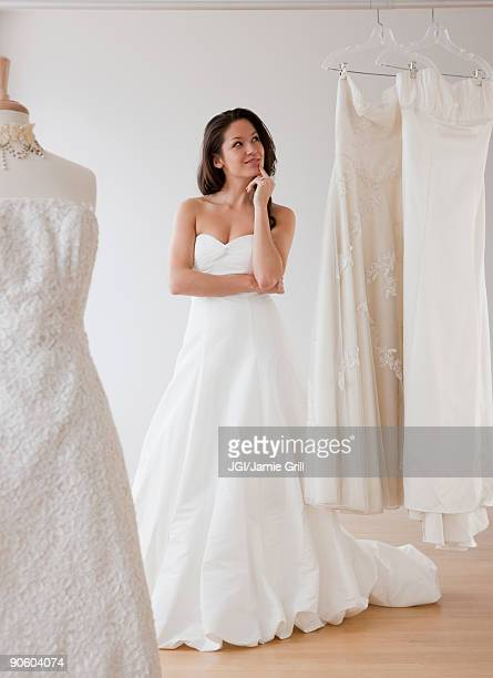 mixed race woman trying on wedding dresses - strapless dress stock pictures, royalty-free photos & images