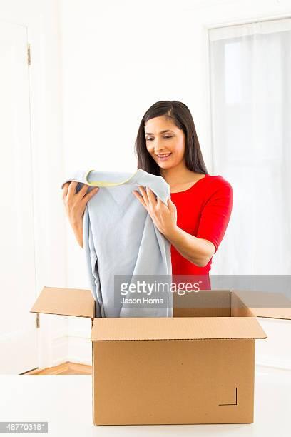 Mixed race woman unpacking cardboard box