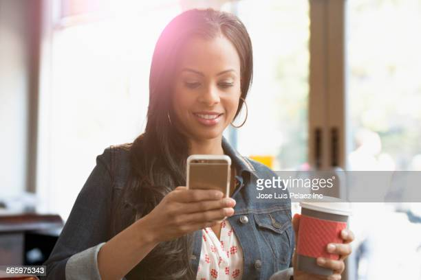 Mixed race woman using cell phone in coffee shop