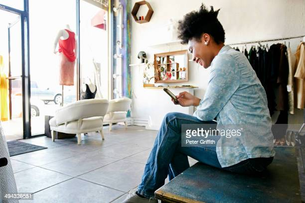 Mixed race woman using cell phone in store