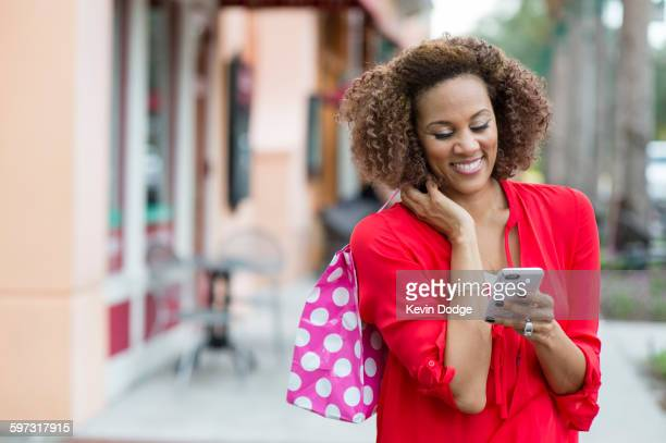 Mixed race woman using cell phone outdoors
