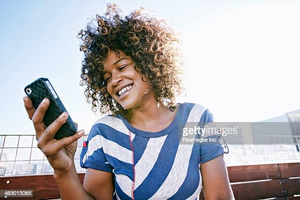 mixed race woman using cell phone - pacific islander stock pictures, royalty-free photos & images