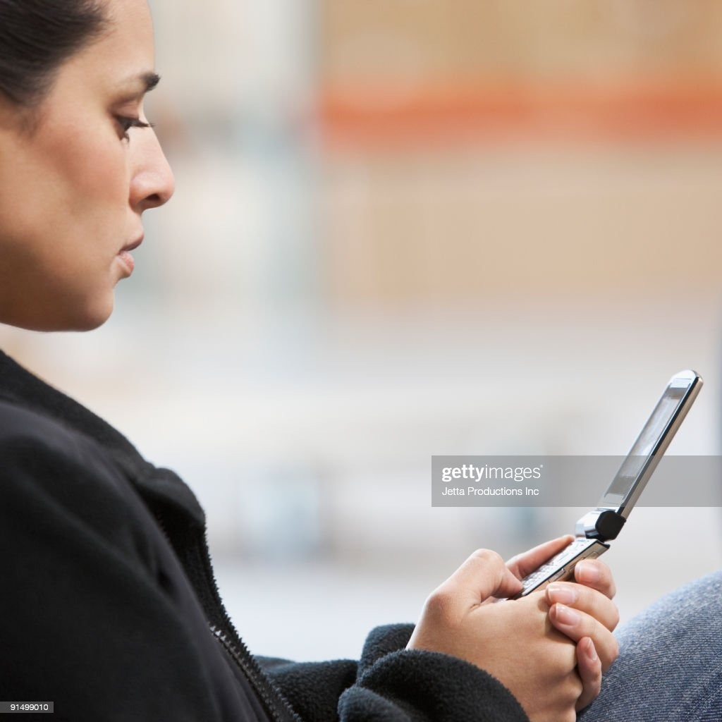 Mixed race woman using cell phone : Stock-Foto