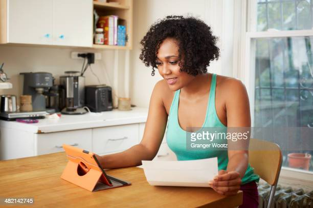 Mixed race woman using digital tablet in kitchen