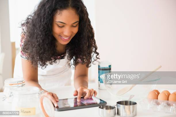 Mixed race woman using digital tablet while cooking
